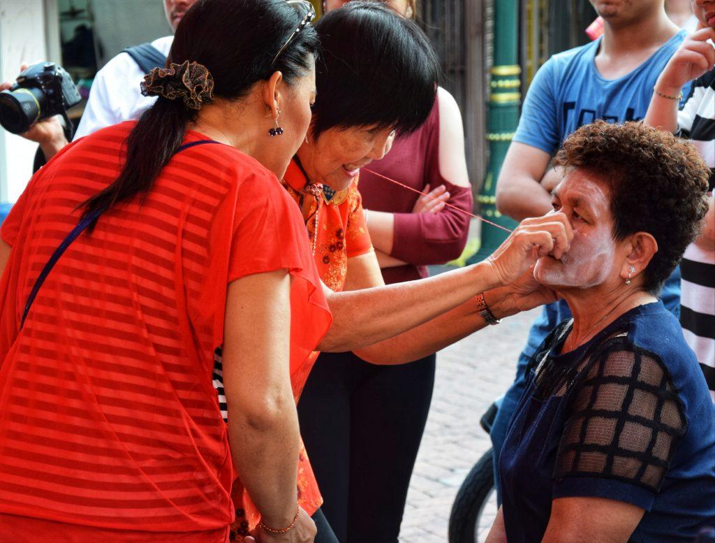 Traditionelle Gesichtsenthaarung mit der Fadentechnik während des Festes